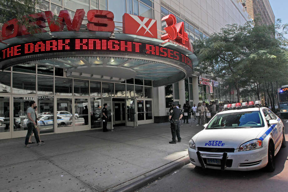 """Police officers stand guard as people line up for a screening of the new Batman movie at a theatre in midtown, Saturday, July 21, 2012 in New York. Security was stepped up in theatres around the U.S. during showings of the new Batman movie, """"The Dark Knight Rises """" after twelve people were killed and dozens were injured in a shooting attack early Friday in Aurora, Colo. Police have identified the suspected shooter as James Holmes, 24. (AP Photo/Mary Altaffer) / AP"""