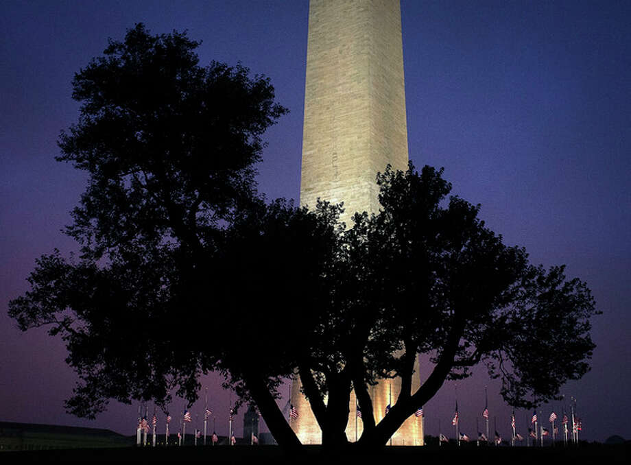 Flags around the Washington Monument in Washington, fly at half-staff early Saturday, July 21, 2012, in tribute to the victims of the deadly mass shooting in Aurora, Colo. (AP Photo/J. David Ake) / AP