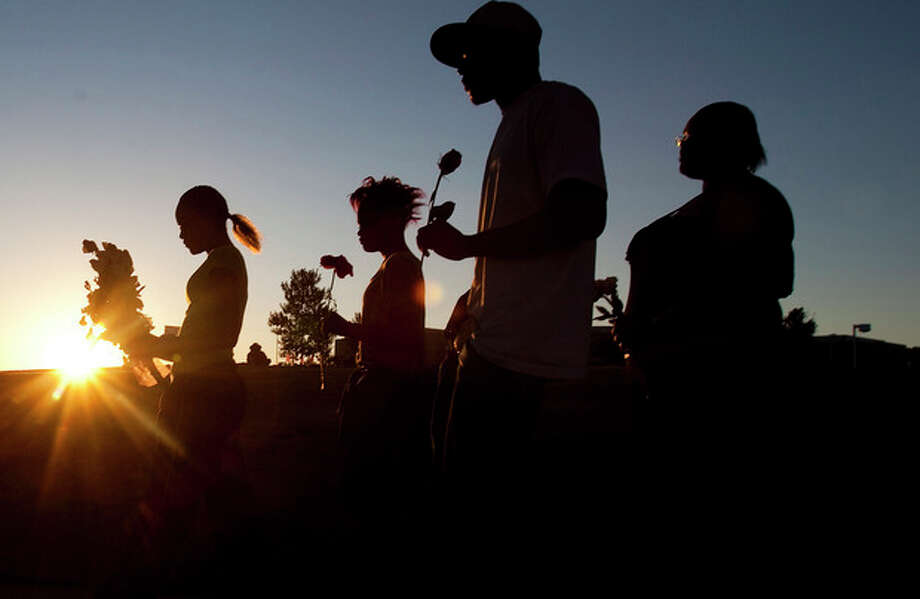 """From left, Tylecia Amos, 14, Shatyra Amos, 15, Michael Walker, 17, and Mykia Walker, 16, carry flowers to lay at a makeshift memorial across the street from the Century Theater parking lot, on Saturday, July 21, 2012 in Aurora, Colo. Twelve people were killed and dozens were injured in the attack early Friday at the packed theater during a showing of the Batman movie, """"Dark Knight Rises."""" Police have identified the suspected shooter as James Holmes, 24. (AP Photo/Barry Gutierrez) / FR170088 AP"""