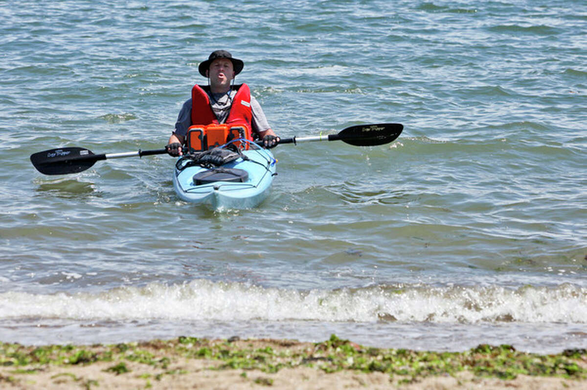 Eric Cott takes a deep breath as he arrives at Shady Beach after completing the journey across Long Island Sound for Kayak for a Cause on Saturday. Hour Photo / Chris Palermo