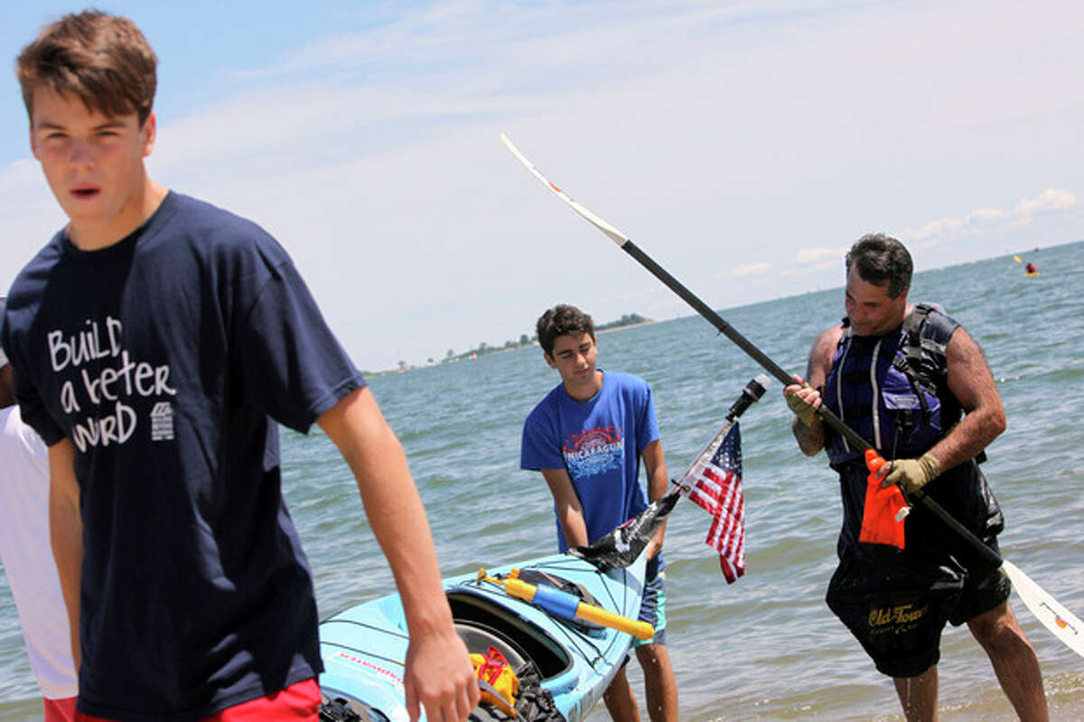 """Hour photo / Chris Palermo Top, Gregg Lachterman inspects his paddle as volunteers carry his kayak up the beach after arriving at Shady Beach, completing the journey across Long Island Sound for """"Kayak for a Cause"""" on Saturday. Below, Volunteers carry a kayak up the beach."""