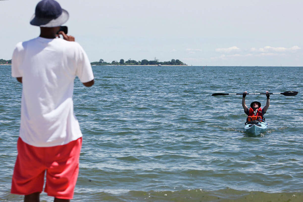 Eric Cott raises his hands in victory after completing the journey across Long Island Sound for Kayak for a Cause as Shady Beach on Saturday. Hour Photo / Chris Palermo