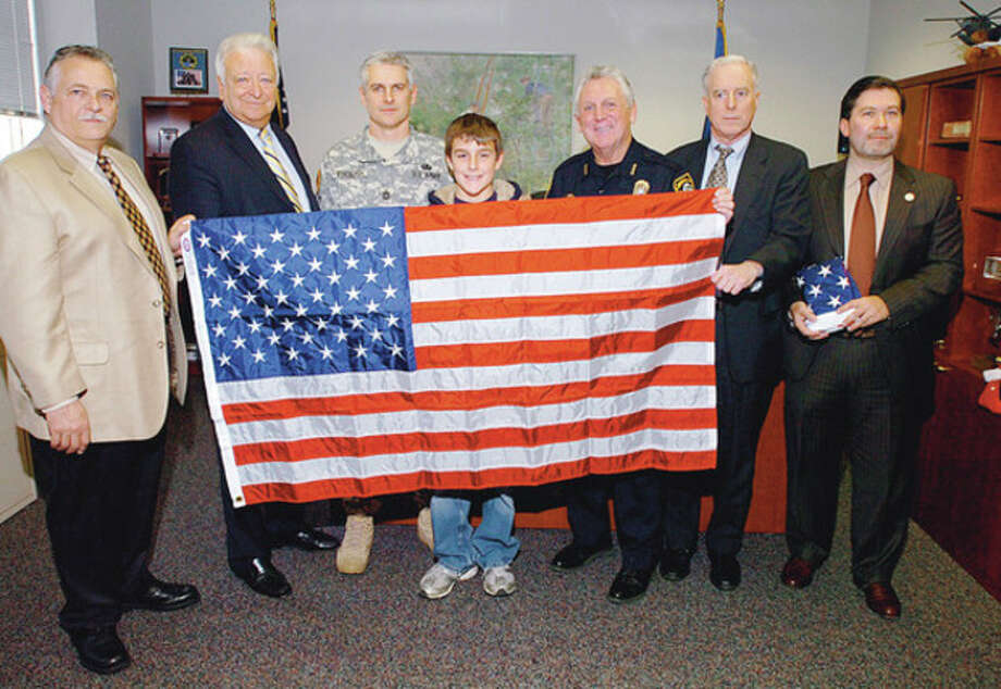 Hour photo / Erik Trautmann Above, Norwalk Police Commssioner Peter Torrano, Mayor Richard A. Moccia, Norwalk police officer and Army Reserve Sgt. Patrick English and his son, Luke, Police Chief Harry Rilling, Police Commssioner Dan O'Connor and Police Union President Thomas Roncinske unfurl a flag that English presented them Thursday that he had flown over the U.S. embassy while stationed in Iraq. Below, a declaration stating that a U.S. flag flew over the American Embassy in Baghdad. / (C)2011, The Hour Newspapers, all rights reserved