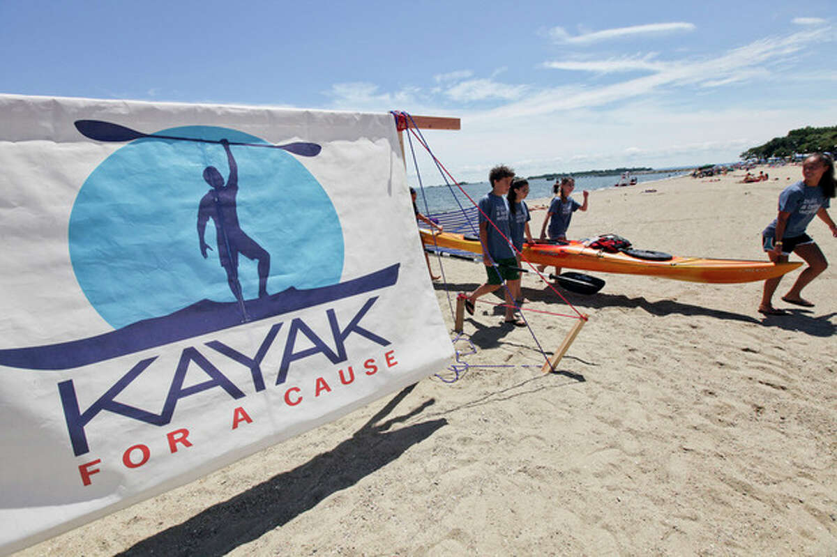 Volunteers carry a Kayak up the beach after the a Kayaker finished the journey across Long Island Sound during Kayak for a cause on Saturday at Shady Beach. Hour Photo / Chris Palermo