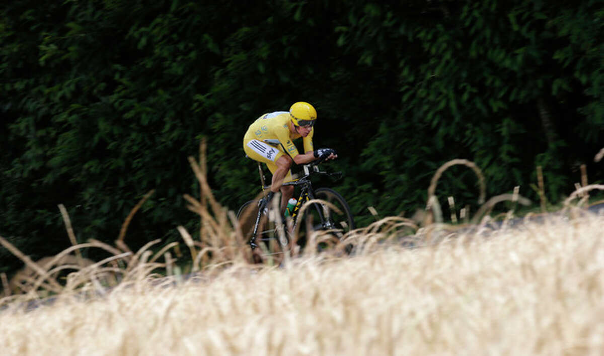 Bradley Wiggins of Britain, wearing the overall leader's yellow jersey, strains on his way to win the 19th stage of the the Tour de France cycling race, an individual time trial over 53.5 kilometers (33.2 miles) with start in Bonneval and finish in Chartres, France, Saturday July 21, 2012. (AP Photo/Christophe Ena)