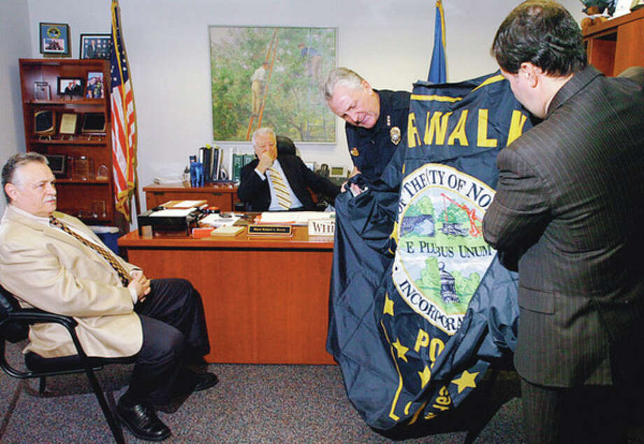 Hour photo / Erik Trautmann Norwalk Police Chief Harry Rilling and Police Union President Thomas Roncinske unfurl a flag for Police Commissioner Peter Torrano and Mayor Richard Moccia Thursday that Norwalk police officer and Army Reserve Sgt. Patrick English flew over the U.S. embassy when stationed in Iraq. See story Page A3. / (C)2011, The Hour Newspapers, all rights reserved