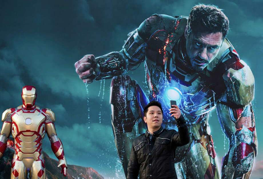 "FILE - In this April 6, 2013 file photo, a Chinese man uses a smartphone to take his own photo with an ""Iron Man"" poster together with a costumed figure, left, during a promotional event of the new movie ""Iron Man 3"" at the Imperial Ancestral Temple in Beijing's Forbidden City. From demanding changes in plot lines that denigrate the Chinese leadership, to dampening lurid depictions of sex and violence, Beijing is having increasing success in pressuring Hollywood into deleting movie content Beijing finds objectionable. It's even getting American studios to sanction alternative versions of films specially tailored for Chinese audiences, like ""Iron Man 3,"" which debuts in theaters around the world later this week. The Chinese version features local heartthrob Fan Bingbing - absent from the version showing abroad - and lengthy clips of Chinese scenery that local audiences love. (AP Photo/Andy Wong, File) / AP"