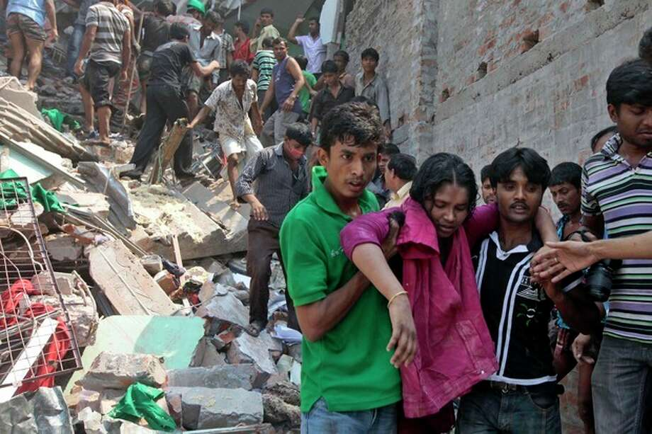 Rescuers assist an injured woman after an eight-story building housing several garment factories collapsed in Savar, near Dhaka, Bangladesh, Wednesday, April 24, 2013. Dozens were killed and many more are feared trapped in the rubble. (AP Photo/ A.M. Ahad) / AP