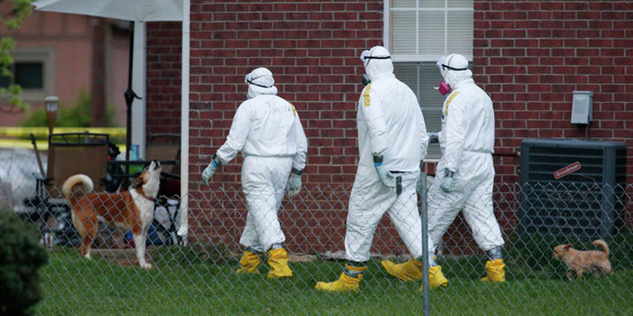 Federal agents wearing hazmat suits inspect the grounds around the house owned by Everett Dutschke, in connection with the recent ricin attacks, as one of his dogs howls Tuesday, April 23, 2013 in Tupelo, Miss. No charges have been filed against Dutschke and he hasn't been arrested. (AP Photo/Rogelio V. Solis) / AP