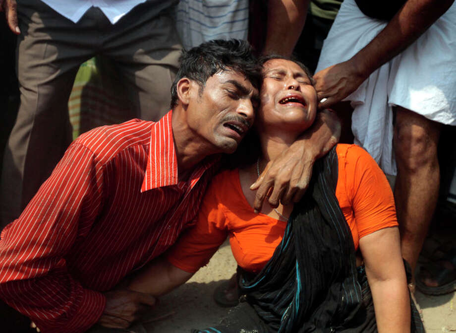 Relatives mourn a victim at the site where an eight-story building housing several garment factories collapsed in Savar, near Dhaka, Bangladesh, Wednesday, April 24, 2013. The building collapsed near Bangladesh's capital Wednesday morning, killing dozens of people and trapping many more in the rubble, officials said. (AP Photo/ A.M. Ahad) / AP