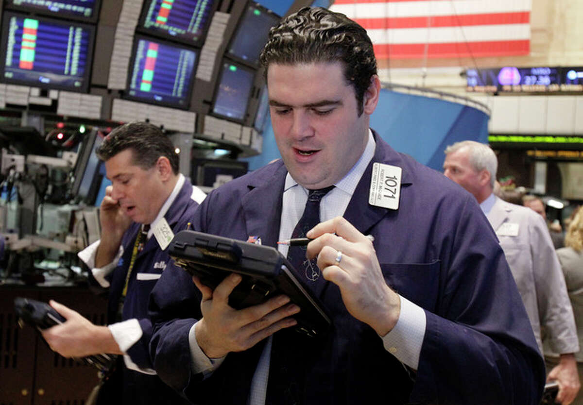 In this Dec. 9, 2011 photo, trader Robert McQuade, right, works on the floor of the New York Stock Exchange. European markets edged tentatively higher Monday, De. 19, 2011, stabilizing after losses in Asia, as investors weighed the potential consequences of the death of North Korea's absolute ruler, Kim Jong Il. (AP Photo/Richard Drew)