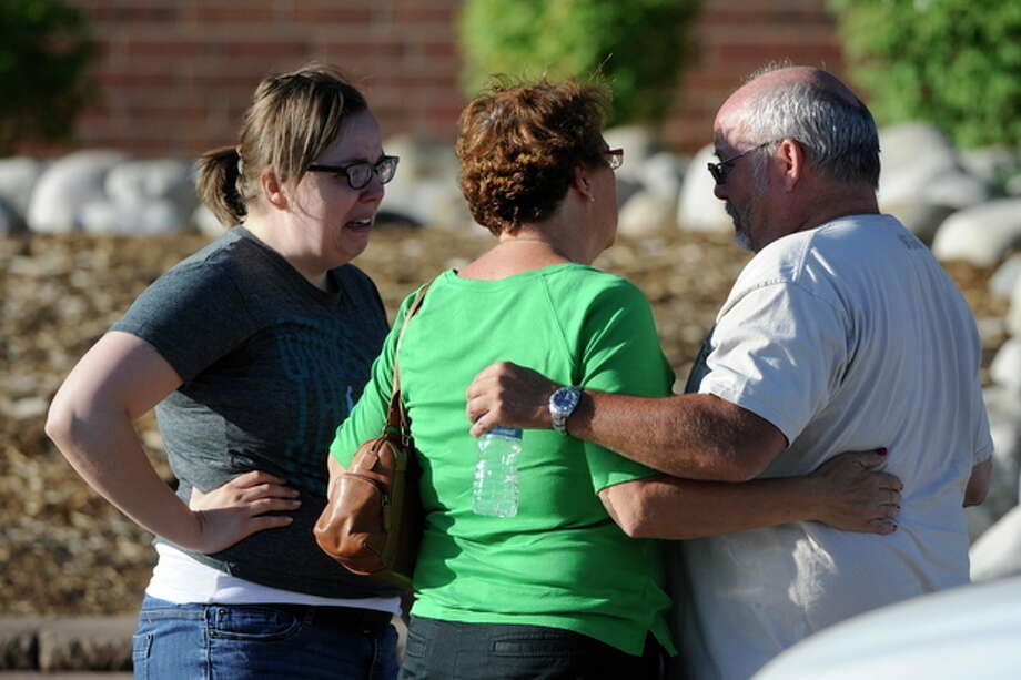 Tom Sullivan talks with family members at Gateway High School in Aurora, Colo., where witnesses we being interviewed by authorities Friday July 20, 2012. A gunman wearing a gas mask set off an unknown gas and fired into the crowded movie theater killing 12 people and injuring at least 50 others, authorities said. (AP Photo/The Denver Post, Craig F. Walker) TV, INTERNET AND MAGAZINES CALL FOR RATES AND TERMS / The Denver Post