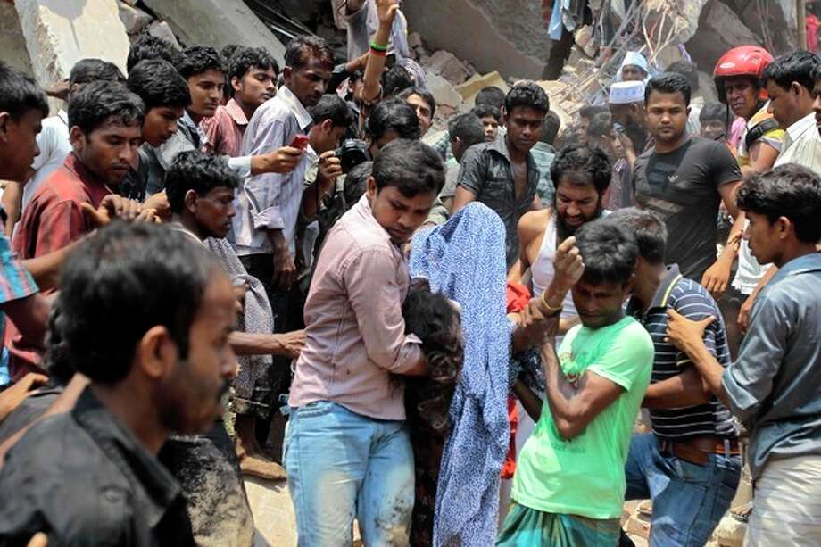 Rescue workers carry a victim's body after an eight-story building housing several garment factories collapsed in Savar, near Dhaka, Bangladesh, Wednesday, April 24, 2013. Dozens were killed and many more are feared trapped in the rubble. (AP Photo/ A.M. Ahad) / AP
