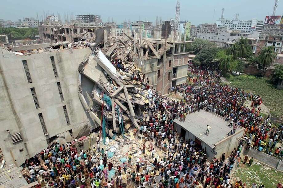 People and rescuers gather after an eight-story building housing several garment factories collapsed in Savar, near Dhaka, Bangladesh, Wednesday, April 24, 2013. Dozens were killed and many more are feared trapped in the rubble. (AP Photo/ A.M. Ahad) / AP