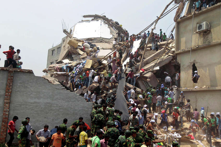 Rescue workers and people look for survivors after an eight-story building housing several garment factories collapsed in Savar, near Dhaka, Bangladesh, Wednesday, April 24, 2013. Dozens were killed and many more are feared trapped in the rubble. (AP Photo/ A.M. Ahad) / AP