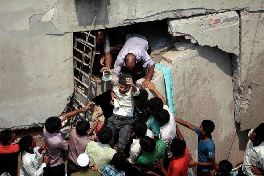 A man who was trapped in an eight-story building housing several garment factories is rescued after the structure collapsed in Savar, near Dhaka, Bangladesh, Wednesday, April 24, 2013. The building collapsed near Bangladesh's capital Wednesday morning, killing dozens of people and trapping many more in the rubble, officials said. (AP Photo/ A.M. Ahad) / AP