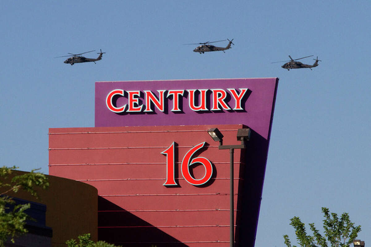 """AP photo / Barry Gutierrez Three helicopters make a flyover of the Century Theater on Saturday in Aurora, Colo. Twelve people were killed and dozens were injured in the attack early Friday at the packed theater during a showing of the Batman movie, """"Dark Knight Rises."""" Police have identified the suspected shooter as James Holmes, 24."""