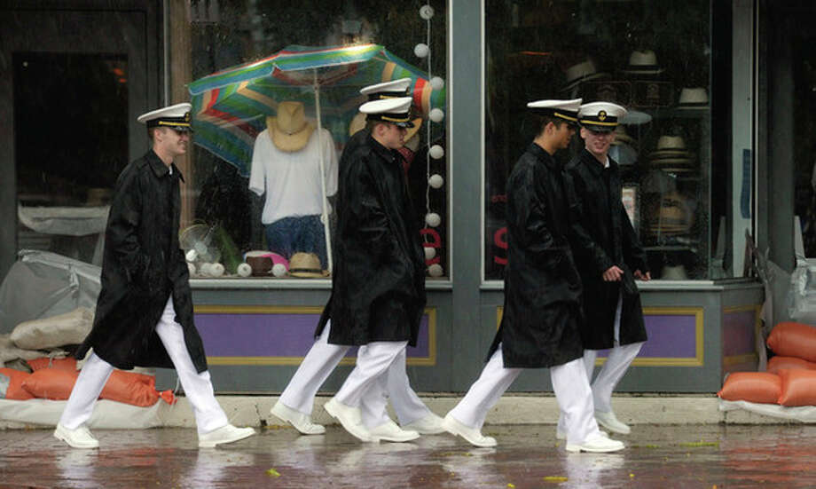 Naval Academy midshipmen walk in downtown Annapolis, Md., during Hurricane Irene, Saturday, Aug. 27, 2011. (AP Photo/Susan Walsh) / AP