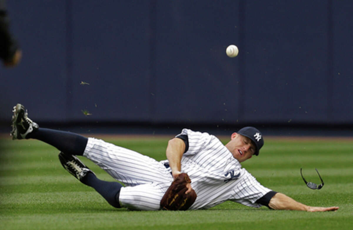New York Yankees center fielder Brett Gardner (11) loses his glasses on Baltimore Orioles' Nate McLouth's fourth-inning double during a baseball game at Yankee Stadium in New York, Saturday, April 13, 2013. (AP Photo/Kathy Willens)