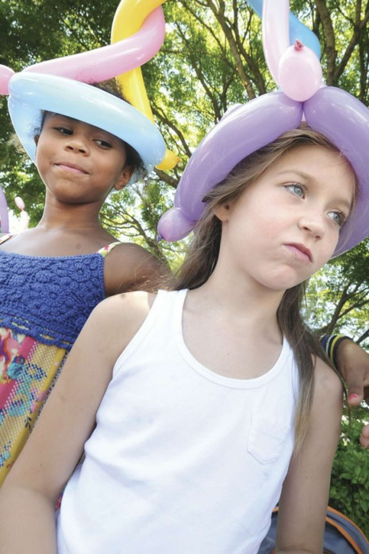 From left, Afou Hession, 8, and Julia Rubino, 7, don balloon hats at the Westport Fine Arts Festival.