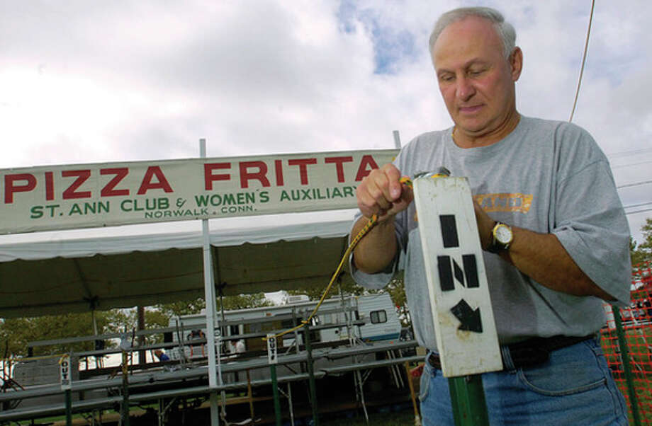 Ken Romano helps set up the St. Ann' Pizza Fritta booth at Veteran's Park Thursday in preparation for this year's Norwalk Seaport Association Oyster Festival. / (C)2011, The Hour Newspapers, all rights reserved