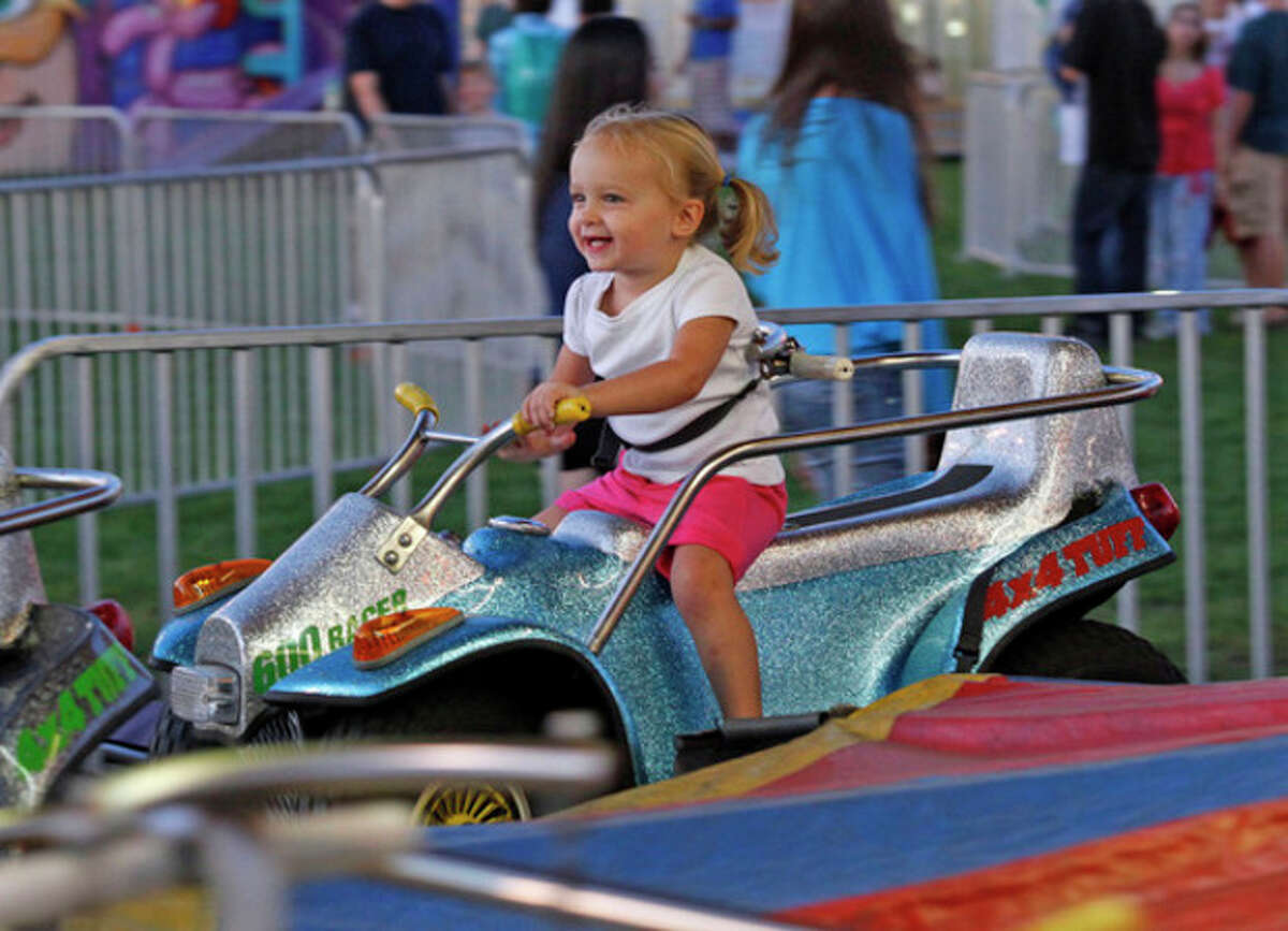 Liza Fogelson, 2 1/2, enjoys a ride at the Oyster Festival Friday evening.