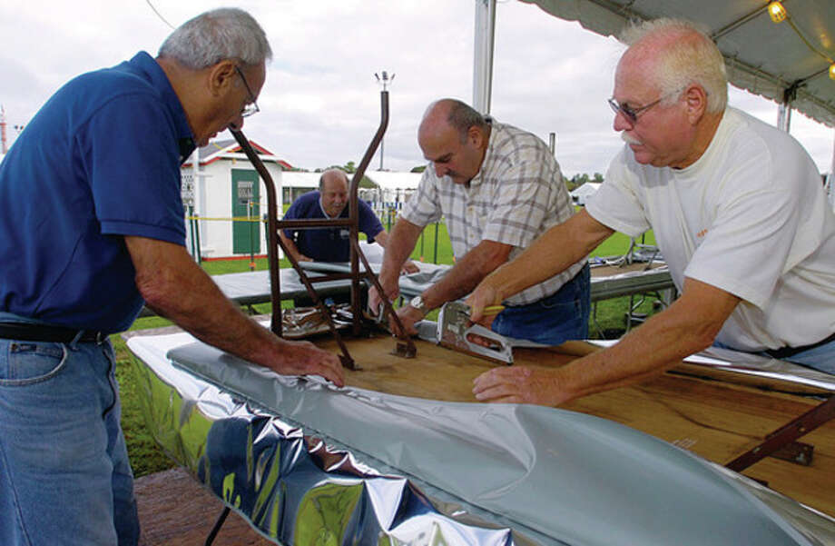 Salvatore Santella, Joe Valiante, Carlo Santella and Ken Prince help set up the St. Ann' Pizza Fritta booth at Veteran's Park Thursday in preparation for this year's Norwalk Seaport Association Oyster Festival. / (C)2011, The Hour Newspapers, all rights reserved