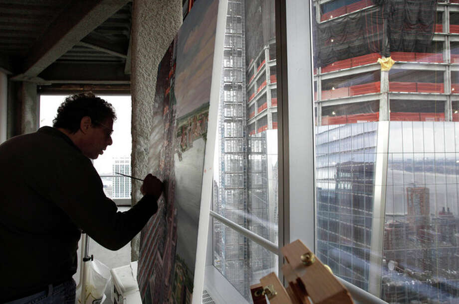 In this Aug. 25, 2011 photo, artist Todd Stone paints in his studio with a view of One World Trade Center, right, in New York. Stone is among the artists who are showing their works in exhibitions commemorating the 10th anniversary of the terrorist attacks. At least two dozen Sept. 11-related museum and gallery exhibitions are being presented throughout the city. (AP Photo/Mark Lennihan) / AP