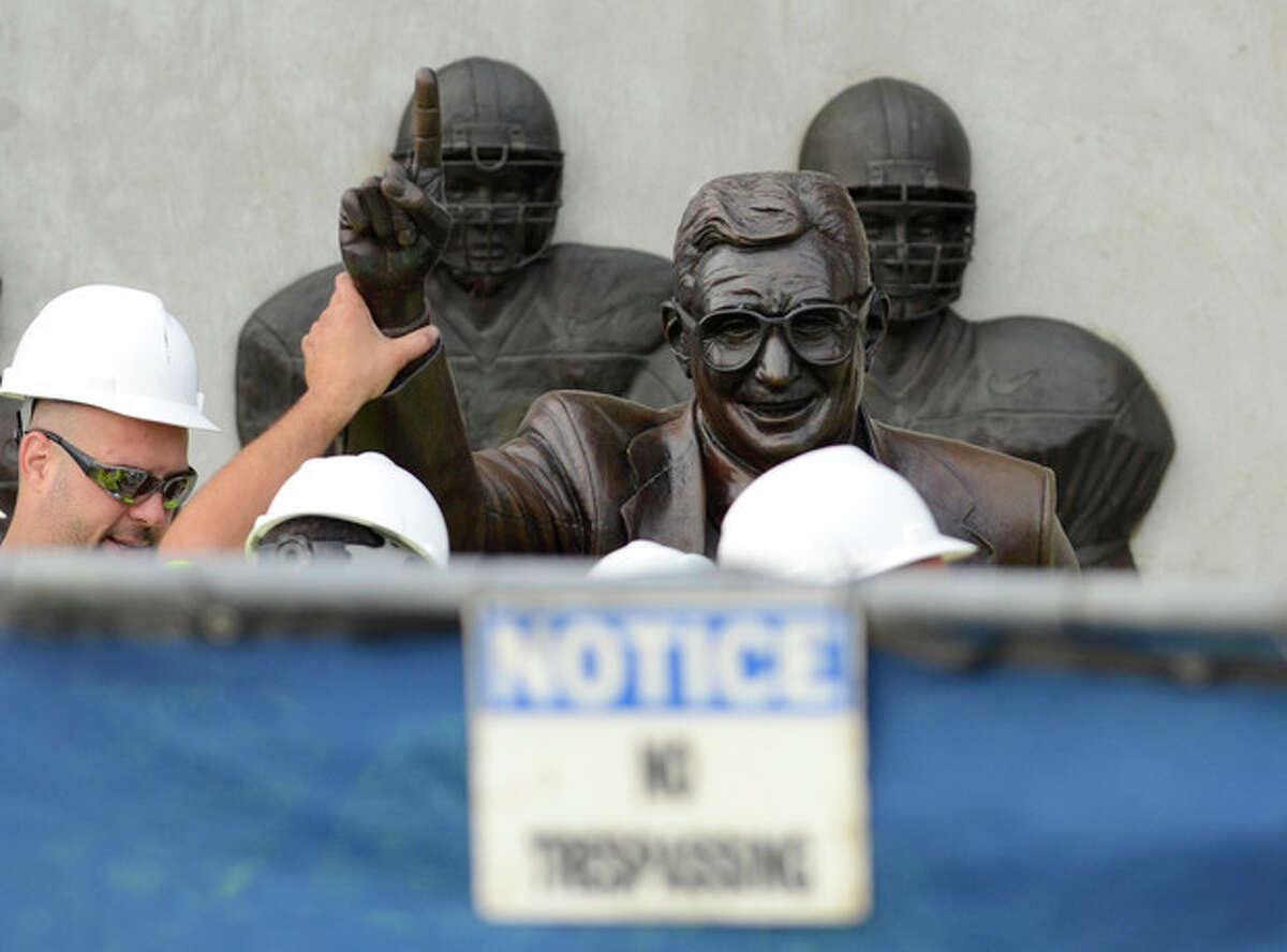 Workers handle the statue of former Penn State football coach Joe Paterno before removing the statue Sunday, July 22, 2012, in State College, Pa. The famed statue of Paterno was taken down from outside the Penn State football stadium Sunday, eliminating a key piece of the iconography surrounding the once-sainted football coach accused of burying child sex abuse allegations against a retired assistant. (AP Photo/John Beale)