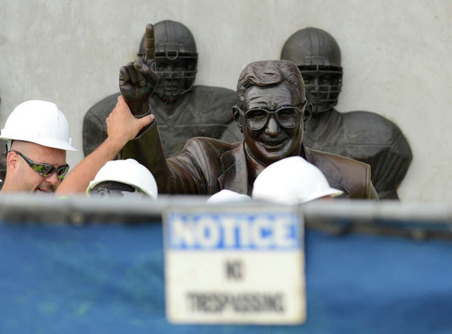 Workers handle the statue of former Penn State football coach Joe Paterno before removing the statue Sunday, July 22, 2012, in State College, Pa. The famed statue of Paterno was taken down from outside the Penn State football stadium Sunday, eliminating a key piece of the iconography surrounding the once-sainted football coach accused of burying child sex abuse allegations against a retired assistant. (AP Photo/John Beale) / FR157268 AP