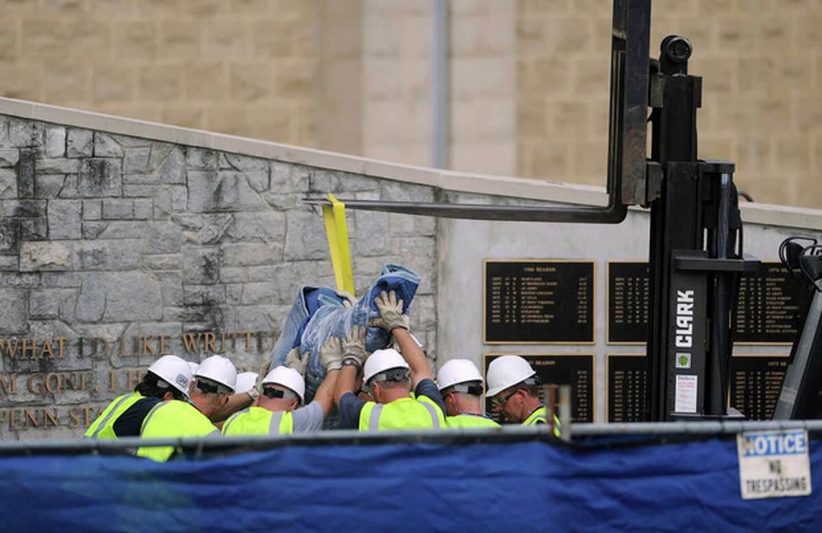 The statue of former Penn State football coach Joe Paterno is moved inside a garage at Beaver Stadium in State College, Pa., on Sunday, July 22, 2012. The university announced earlier Sunday that it was taking down the monument in the wake of an investigative report that found the late coach and three other top Penn State administrators concealed sex abuse claims against retired assistant coach Jerry Sandusky. (AP Photo/Centre Daily Times, Christopher Weddle) MANDATORY CREDIT; MAGS OUT