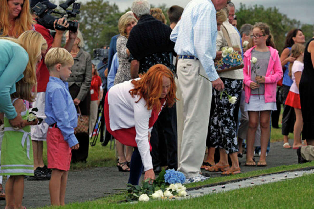 A girl places flowers on the memorial stone of her father during the Connecticut Remembers Steptember 11th Memorial Service held at Sherwood Island State Park Thursday evening.