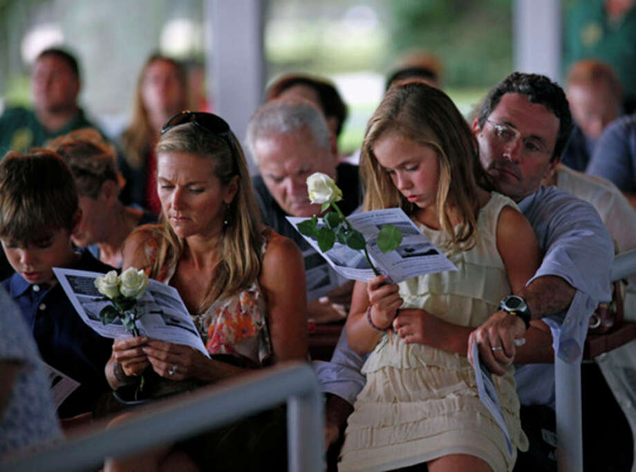 A family looks on as victim's names are read during the Connecticut Remembers Steptember 11th Memorial Service held at Sherwood Island State Park Thursday evening.