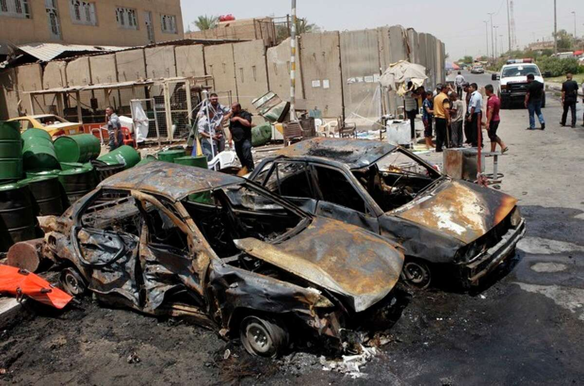 People inspect the aftermath of a car bomb attack in Baghdad's Shiite enclave of Sadr City, Iraq, Monday, July 23, 2012. An onslaught of bombings and shootings killed scores of people across Iraq on Monday, in the nation's deadliest day so far this year. The attacks come days after the leader of al-Qaida in Iraq declared a new offensive seeking to re-assert its might in the security vacuum left by the departing Americans. (AP Photo/Karim Kadim)