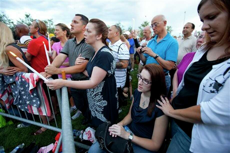 "Anne Marie Hochhalter, 30, second from right, and her friend Roxy Chesser, 30, right, attend a prayer vigil, held to remember the lost and injured in Friday's mass shooting at a movie theater, in a park outside the Aurora Municipal Center in Aurora, Colo., Sunday July 22, 2012. Hochhalter, a paralyzed victim of the Columbine High School tragedy over 12 years ago, and other survivors of the 1999 massacre reached out to people who survived the theater shooting. Twelve people were killed and dozens were injured in a shooting attack Friday at the packed theater during a showing of the Batman movie, ""The Dark Knight Rises."" Police have identified the suspected shooter as James Holmes. (AP Photo/Barry Gutierrez) / FR170088 AP"