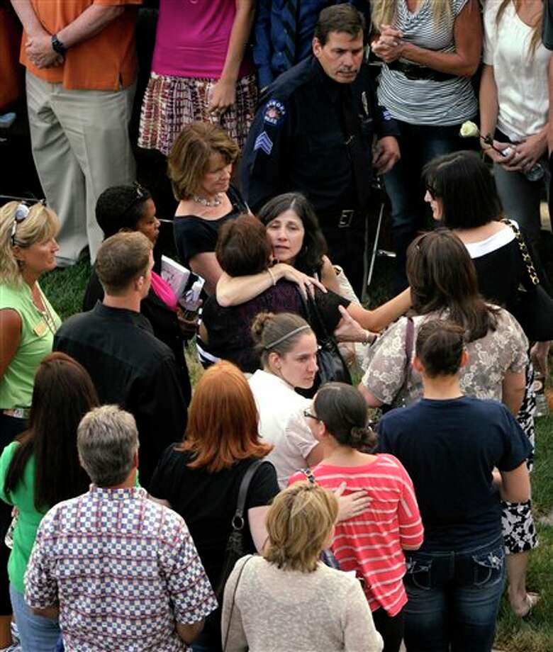 "In this overview, families gather for a prayer vigil honoring the victims of Friday's mass shooting at a movie theater, Sunday, July 22, 2012, at the Aurora Municipal Center campus in Aurora, Colo. Twelve people were killed and dozens were injured in a shooting attack early Friday at the packed theater during a showing of the Batman movie, ""The Dark Knight Rises."" Police have identified the suspected shooter as James Holmes, 24. (AP Photo/The Denver Post, Joe Amon, Pool) / The Denver Post2012"