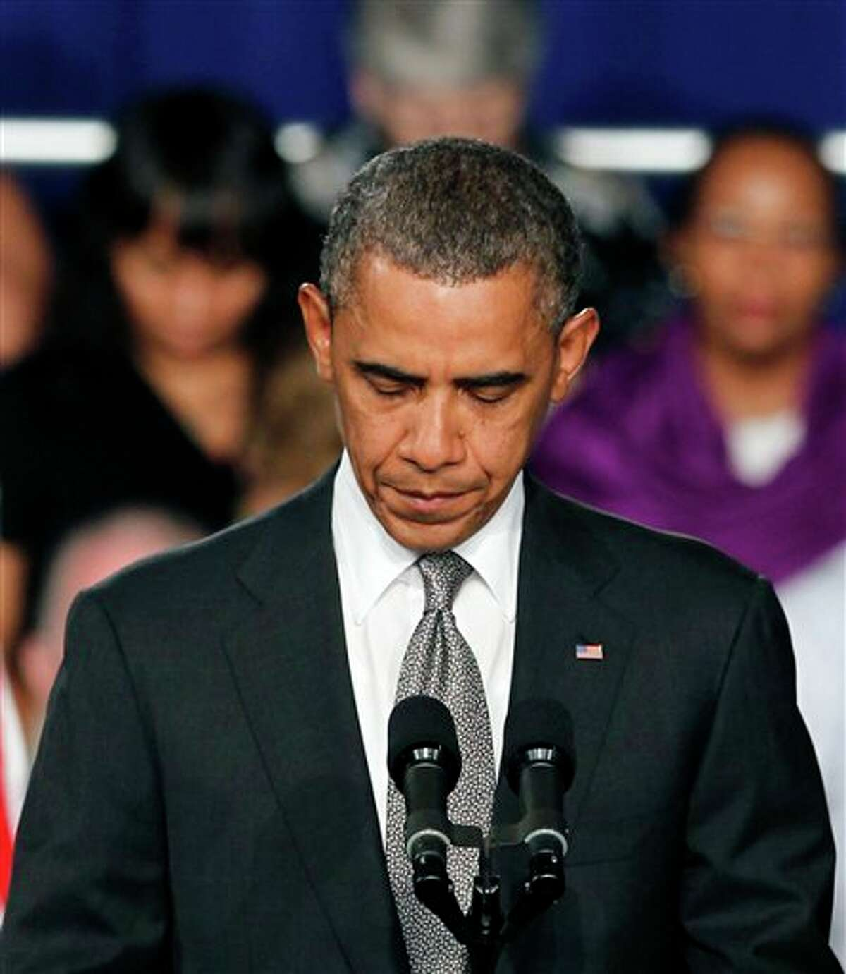 President Barack Obama takes a moment of silence for the events in Colorado at a campaign stop in Fort Myers, Fla., Friday, July 19, 2012. Obama, who was scheduled to spend the day campaigning in Florida, canceled his campaign events to return to Washington to monitor the shooting aftermath. (AP Photo/Alan Diaz)