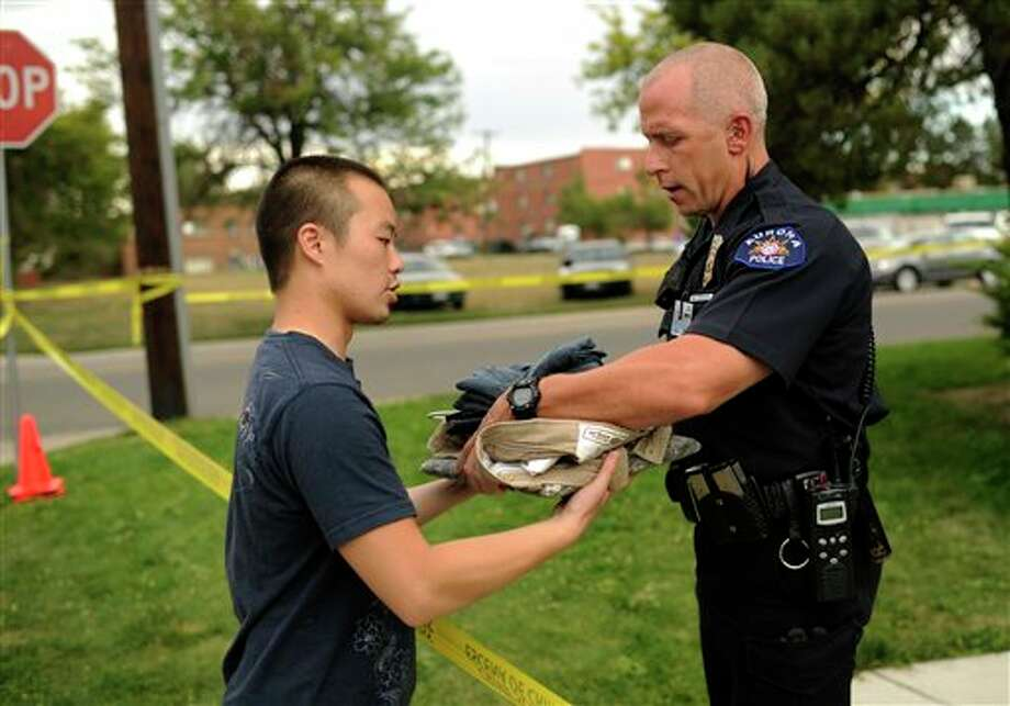 "Apartment resident Ben Leung, left, of University of Colorado medical student, picks up his clothes, Sunday, July 22, 2012, in Aurora, Colo. The apartment of alleged gunman James Holmes was evacuated by Aurora Police. Authorities reported that 12 died and more than three dozen people were shot during an assault at a movie theatre of Friday's premiere of ""The Dark Knight Rises."" (AP Photo/The Denver Post, Hyoung Chang) TV, INTERNET AND MAGAZINES CALL FOR RATES AND TERMS / 2011 The Denver Post"