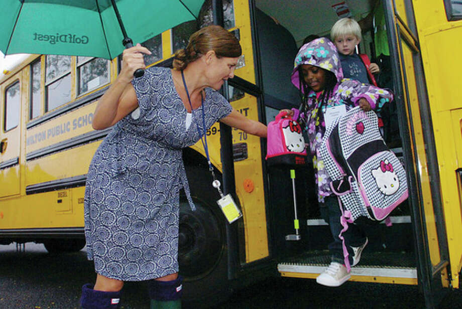 Miller Driscoll School reading aide Mary Jarboe helps kindergartner Savannah Joseph off the bus on the first day of school on Tuesday. Hour photo / Erik Trautmann / (C)2011, The Hour Newspapers, all rights reserved