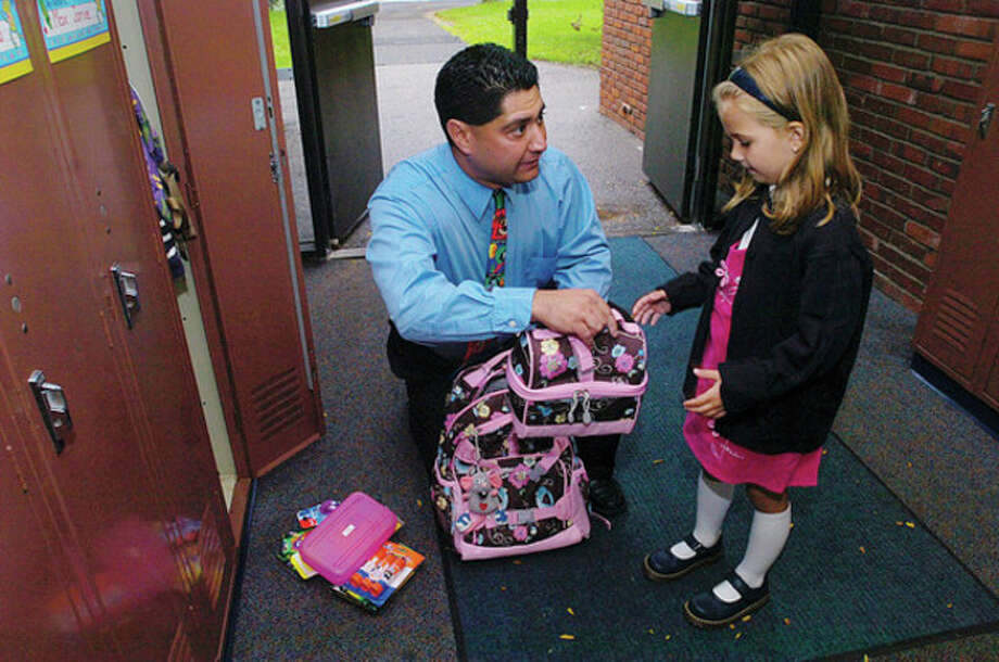 Miller Driscoll School kindergarten teacher Sal Giaimo helps Melanie Rutkowski find her locker on the first day of school on Tuesday. Hour photo / Erik Trautmann / (C)2011, The Hour Newspapers, all rights reserved