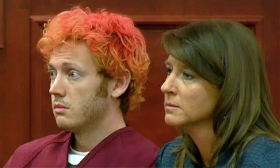 In this image taken from video provided by KUSA.com, James Holmes, left, the suspected gunman in Friday's Colorado theater massacre, makes his first appearance in court with his attorney Tamara Brady in Centennial, Colo. on Monday, July 23, 2012. (AP Photo/KUSA.com) / KUSA.com