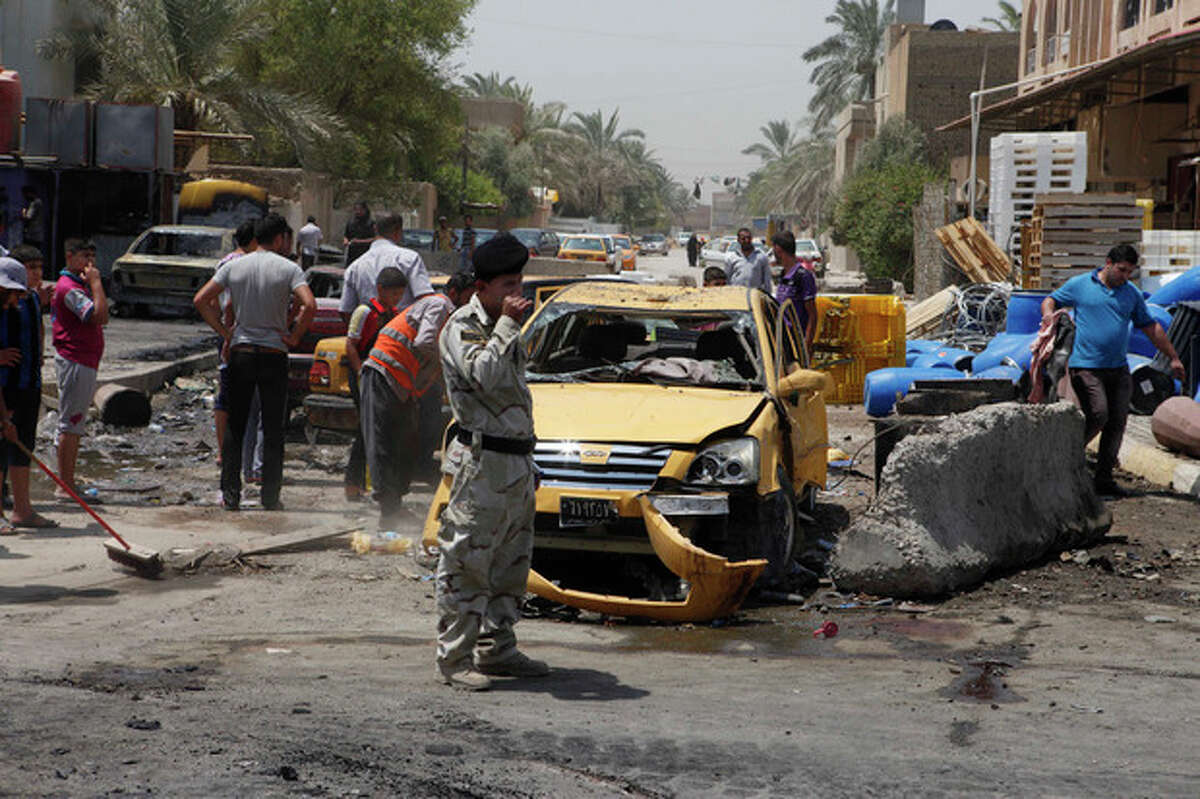 People inspect the aftermath of a car bomb attack in Baghdad's Shiite enclave of Sadr City, Iraq, Monday, July 23, 2012. An onslaught of bombings and shootings has killed scores of people across Iraq on Monday, in the nation's deadliest day so far this year. The attacks come days after the leader of al-Qaida in Iraq declared a new offensive seeking to re-assert its might in the security vacuum left by the departing Americans. (AP Photo/Karim Kadim)