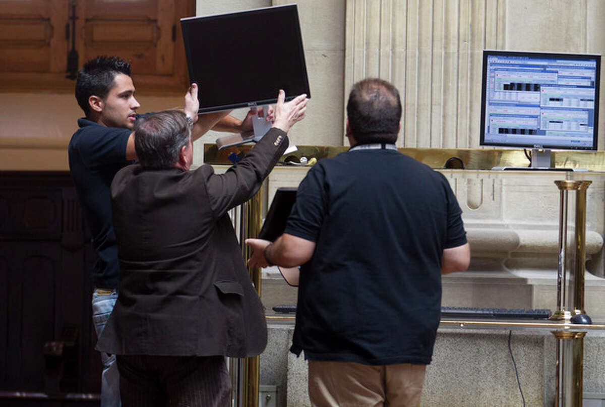 Workers try to get a screen working at the Stock Exchange in Madrid Monday July 23, 2012. The Bank of Spain says the country?'s recession-plagued economy contracted 0.4 percent in the second quarter, a performance even worse than in the first three months of the year.The central bank blamed a big drop in domestic demand: minus 1.2 percent compared to minus 0.5 percent in the first quarter as household and government spending fell at a faster pace. It stressed that these figures were preliminary. (AP Photo/Paul White)