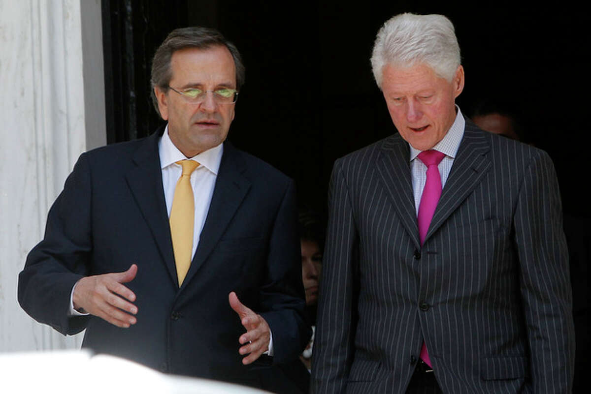 """Greek Prime Minister Antonis Samaras, left, and Former U.S. President Bill Clinton leave Maximos mansion after their meeting in Athens, Sunday, July 22, 2012. Clinton is in Greece to promote the """"Hellenic Initiative,"""" an initiative by businessmen of Greek origin living abroad who want to facilitate foreign investment in the debt-ridden country and to raise (Canadian) $100 million to help charities active in Greece. (AP Photo)"""