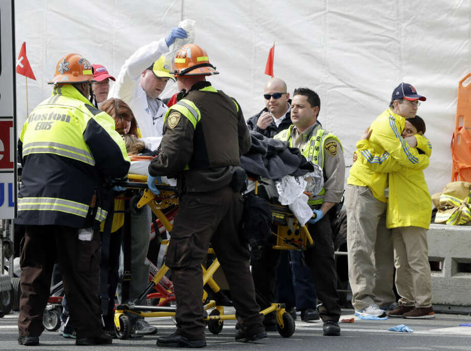 Two Boston Marathon volunteers hug each other, at right, as an injured person is loaded into an ambulance in the aftermath of two blasts which exploded near the finish line of the Boston Marathon in Boston, Monday, April 15, 2013. (AP Photo/Elise Amendola)