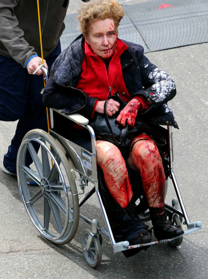 Medical workers aid an injured person at the 2013 Boston Marathon following an explosion in Boston, Monday, April 15, 2013. Two explosions shattered the euphoria of the Boston Marathon finish line on Monday, sending authorities out on the course to carry off the injured while the stragglers were rerouted away from the smoking site of the blasts. (AP Photo/The Boston Globe, David L Ryan)