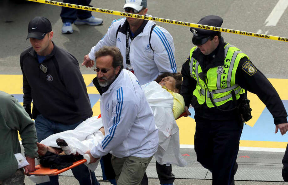 Medical workers aid injured people at the finish line of the 2013 Boston Marathon following an explosion in Boston, Monday, April 15, 2013. Two explosions shattered the euphoria of the Boston Marathon finish line on Monday, sending authorities out on the course to carry off the injured while the stragglers were rerouted away from the smoking site of the blasts. (AP Photo/The Boston Globe, David L Ryan)