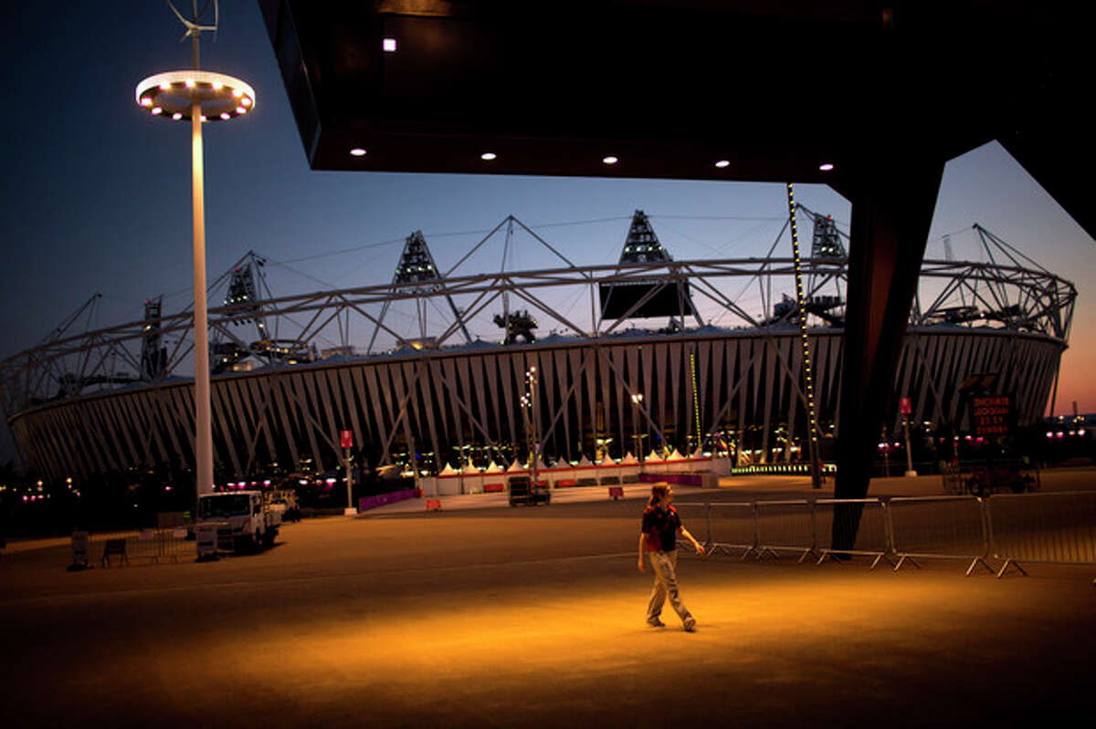 A volunteer walks past the Olympic Stadium at the 2012 Summer Olympics, Sunday, July 22, 2012, in London. The opening ceremonies of the Olympic Games are scheduled for Friday, July 27. (AP Photo/Emilio Morenatti)