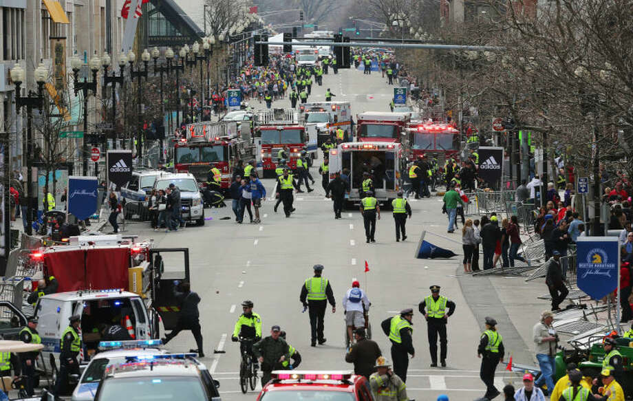 Medical workers respond following an explosion at the 2013 Boston Marathon in Boston, Monday, April 15, 2013. Two explosions shattered the euphoria of the Boston Marathon finish line on Monday, sending authorities out on the course to carry off the injured while the stragglers were rerouted away from the smoking site of the blasts. (AP Photo/The Boston Globe, David L Ryan)