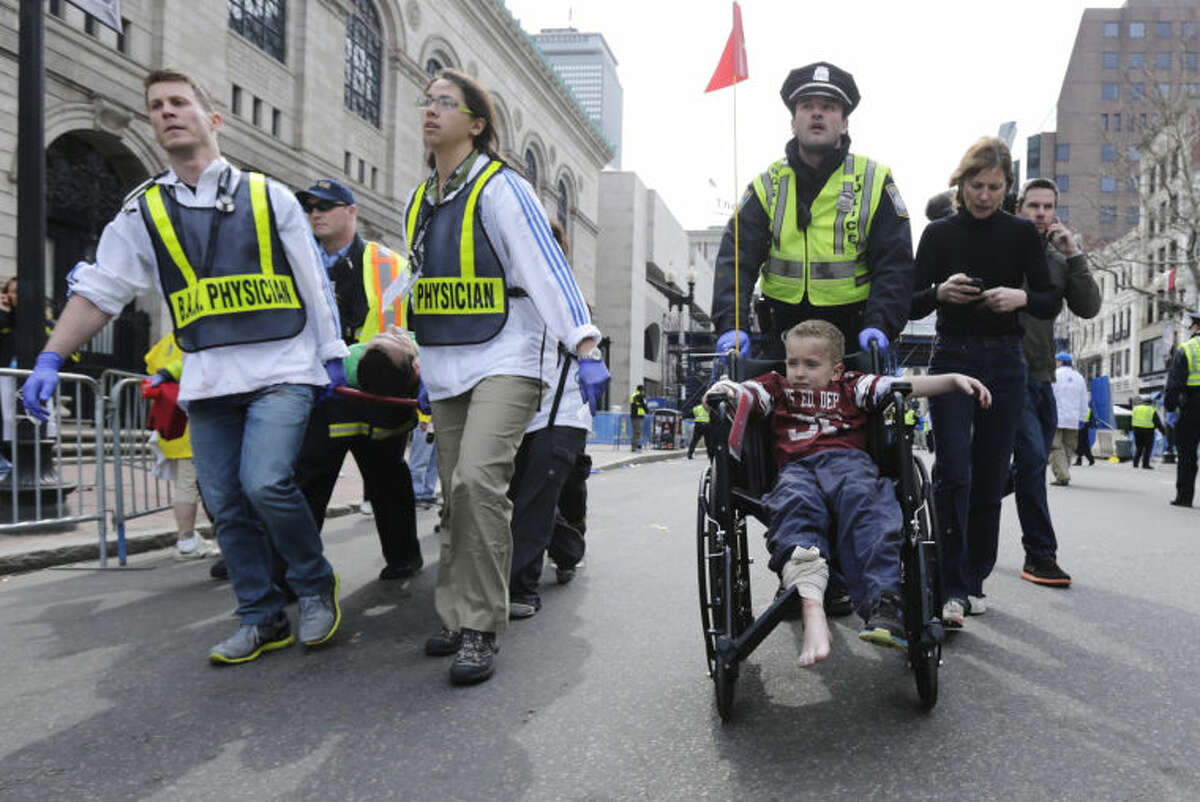 A Boston police officer wheels in injured boy down Boylston Street as medical workers carry an injured runner following an explosion during the 2013 Boston Marathon in Boston, Monday, April 15, 2013. Two explosions shattered the euphoria at the marathon's finish line on Monday, sending authorities out on the course to carry off the injured while the stragglers were rerouted away from the smoking site of the blasts. (AP Photo/Charles Krupa)
